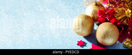 Gorgeous metallic gold christmas baubles, red stars and wrapped present on shiny blue background. Red and gold Christmas banner. - Stock Photo