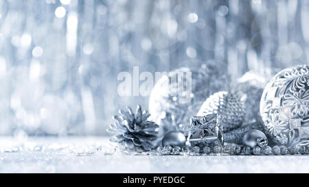 Shiny silver christmas present and beautiful ornaments, with defocused christmas lights in the background. Christmas banner. - Stock Photo