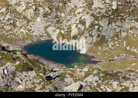 Autumn hiking in Aosta valley, Gressoney, Italy. View of alpine lake of Goudin from Point Sella near the Coda mountain refuge. - Stock Photo