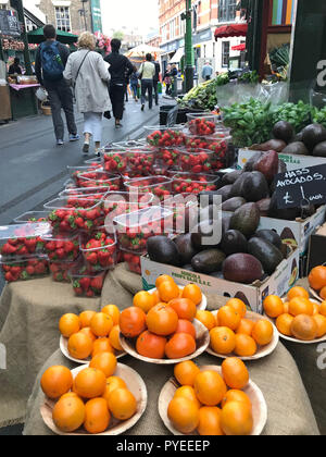 London, UK - October 19, 2018: People walking past a beautiful fruit and vegetable stall on a market in London. - Stock Photo