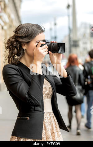 Young woman takes pictures on a city street - Stock Photo
