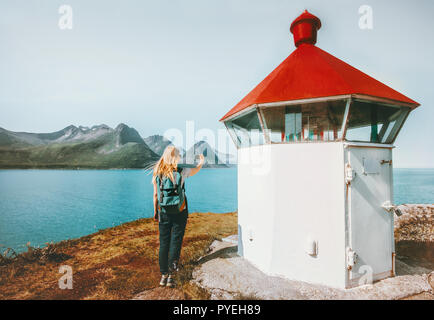 Woman tourist blogging with smartphone taking photo near lighthouse Travel lifestyle adventure summer voyage outdoor in Norway - Stock Photo