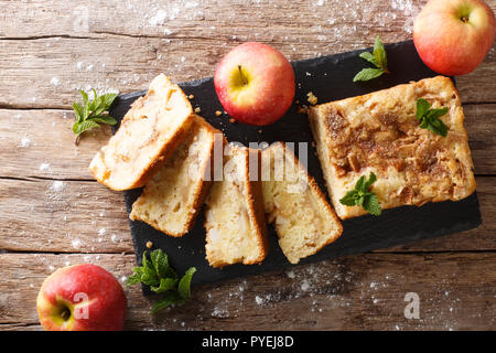 Freshly baked apple bread with cinnamon and mint close-up on the table. Horizontal top view from above - Stock Photo