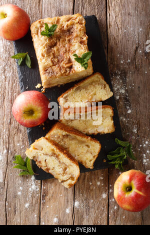 Freshly baked apple bread with cinnamon and mint close-up on the table. Vertical top view from above - Stock Photo