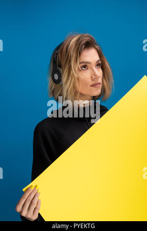 Girl wearing headphones holding a yellow card board. Poster board for advertising with copy space available - Stock Photo