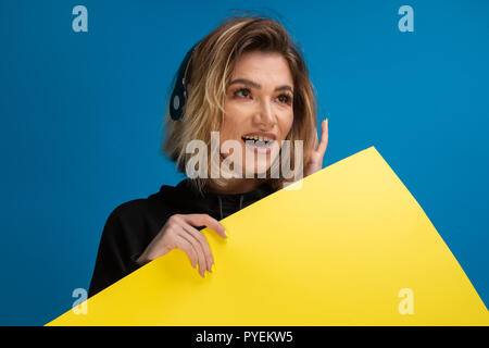 Portrait of woman positively smiling and wearing headphones. Yellow cardboard displayed for advertise. Billboard concept with copy space - Stock Photo