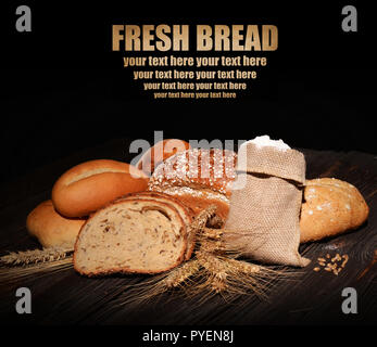 Assortment of fresh bread on black background - Stock Photo