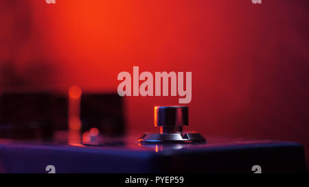 Extremely close up of button for effect electro guitar pedal. Red neon light in night club during show concert - Stock Photo