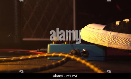 Guitar pedals and footswitch inside recording room. Close up of guitar pedals and musician's foot tapping on it for different sounds. Macro view. - Stock Photo