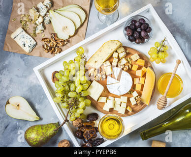 Different types of cheese on wooden board, olive, fruits, almond and wine glasses on white tray. Top view - Stock Photo