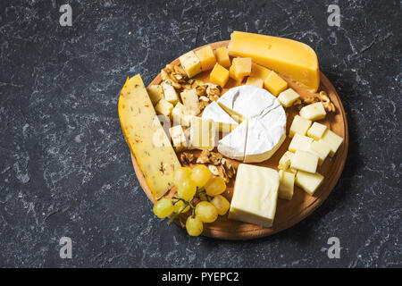 various types of cheese on dark stone table. - Stock Photo