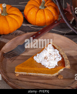 Slice of pumpkin pie with whipped cream topping on a wooden plate with pumpkins in background - Stock Photo
