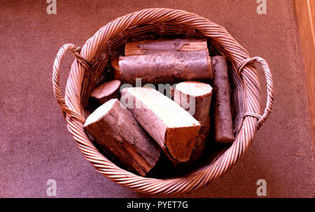 wood logs in whicker basket ready for log burner canterbury kent uk oct 2018 - Stock Photo