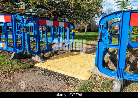 Plastic barriers around holes in the ground where maintenance work is being done, shutting the footpath. - Stock Photo