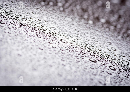 Cloys up to water drops on glass background with color light - Stock Photo