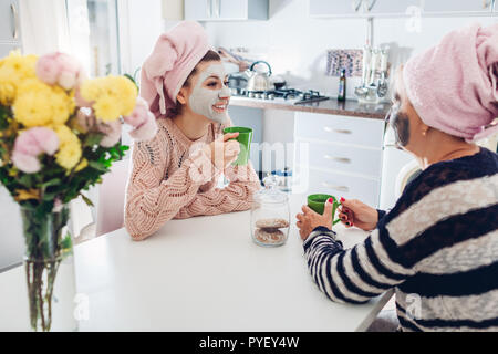 Mother and her adult daughter drinking tea with facial masks applied. Women chilling and talking on kitchen. Family values - Stock Photo