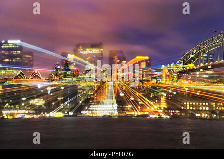 Optical lens effect during long exposure with brightly illuminated Sydney city CBD Landmarks across Harbour from house to the Harbour bridge at sunset - Stock Photo