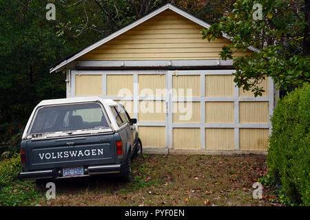 An old blue Volkswagen pickup truck parked outside of a garage. - Stock Photo