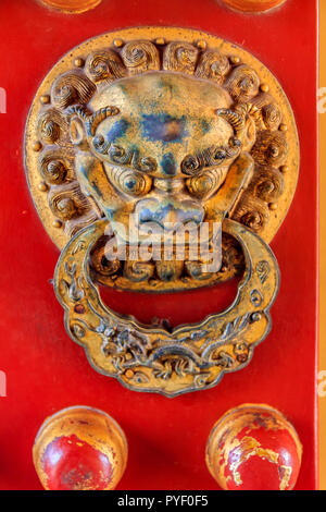Close up of a red wooden door with a lion figurine knocker at the Forbidden City, Beijing - Stock Photo