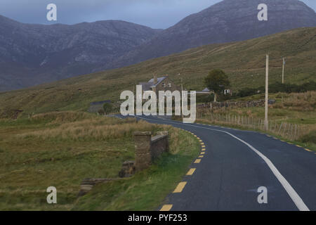 View of a paved rural road traveling through the beautiful landscape of Connemara in the western region of Ireland - Stock Photo