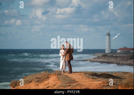 fashionable couple in coats young man and woman on stormy sea coast with white beacon - Stock Photo