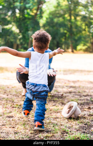 Mother caths happy son who running to her to hug - Stock Photo