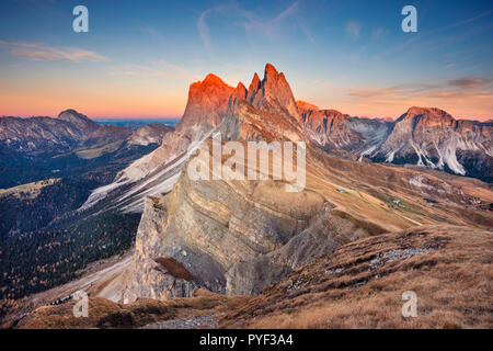 Dolomites. Landscape image of famous Dolomites mountain peaks glowing in beautiful golden evening light at sunset in autumn, South Tyrol, Italy. - Stock Photo