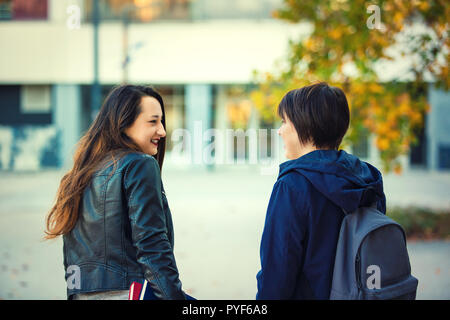 Student friendship as two girls talking and smile outdoors in the college campus. Going to school together, education concept. - Stock Photo