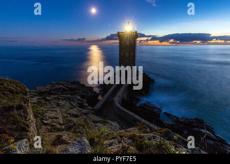 Romantic dusk scenery of lighthouse with moonbeam under the ocean, Kermorvan point, Brittany, France - Stock Photo