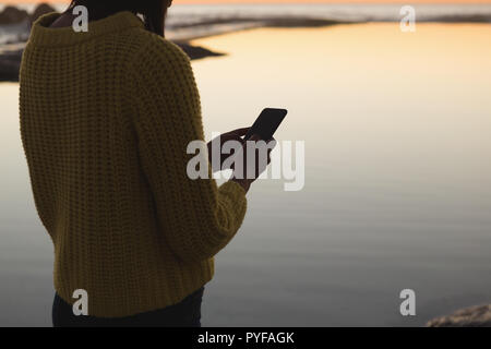 Woman using mobile phone on beach during sunset