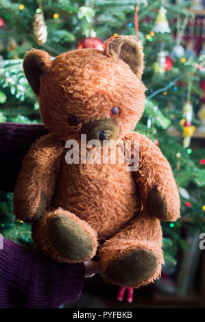 Child hold in hand a vintage stuffed teddy bear toy - its a christmas present. In the background a decorated christmas tree with light garlands and gl - Stock Photo