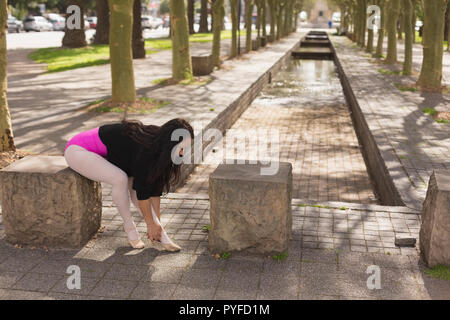 Urban dancer wearing ballet shoes in the city - Stock Photo
