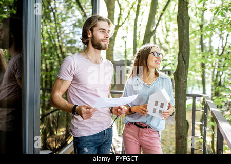 Young creative couple of architechts or designers working with house model and blueprints on the balcony of their office in the forest - Stock Photo
