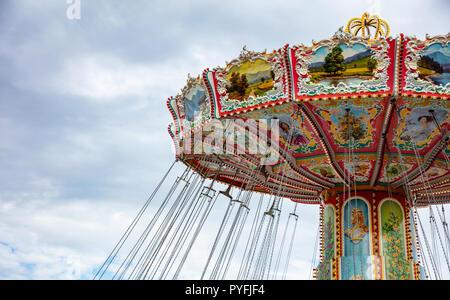 Colorful carousel on cloudy sky background. Oktoberfest, Bavaria, Germany - Stock Photo