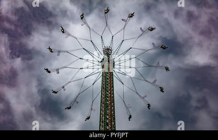 Yo yo carnival ride on cloudy sky background. Oktoberfest, Munich, Germany - Stock Photo