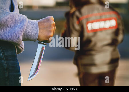 Man in the street with a knife in his hands. The concept of an attack on police officers - Stock Photo