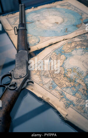 A vintage rifle and a vintage Antarctic region map as a concept of brave expeditions to the North pole - Stock Photo