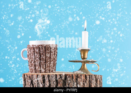 Cup of hot tea in wool scarf and candle in candle stick burning on wood log. It's snowing and blue background. Winter idyll and Christmas holiday - Stock Photo