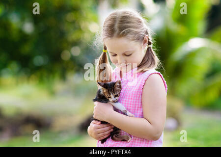 Child holding baby cat. Kids and pets. Little girl hugging cute little kitten in summer garden. Domestic animal in family with kids. Children with hom - Stock Photo