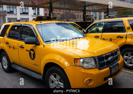 Yellow taxis parked at a Hell's Kitchen gas station in New York City, NY. - Stock Photo
