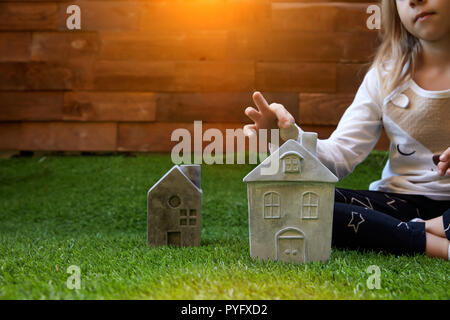 Hand putting coin in house shape piggy bank for saving money to buying a house - Stock Photo