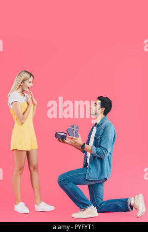 side view of man on bended knee doing marriage proposal to surprised girlfriend gesturing by hands isolated on pink - Stock Photo