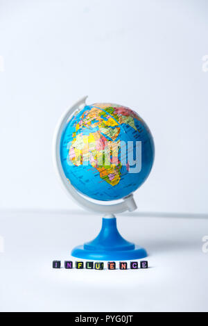text influence, made with small blocks, and globe in background - Stock Photo