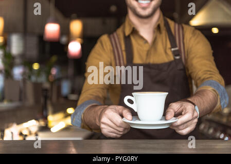 cropped shot of smiling young barista holding cup of coffee - Stock Photo