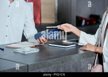 cropped shot of worker holding payment terminal and woman paying with smartphone in shop - Stock Photo