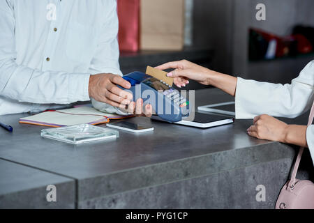 cropped shot of worker holding payment terminal and woman paying with credit card in shop - Stock Photo