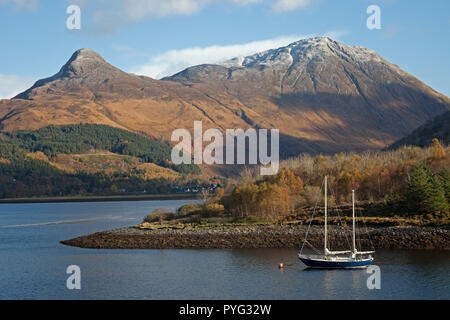 Glen Coe, Lochaber, Scotland, UK. 27 Oct. 2018. UK weather, sunshine in the Scottish Highlands after 0 degrees overnight, first dusting of snow on the mountain  tops of Glencoe this autumn, yacht on Loch Leven with Pap of Glencoe mountain behind - Stock Photo