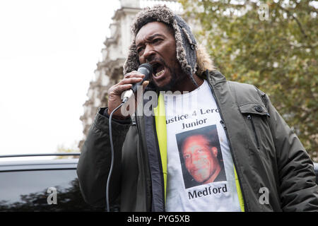 London, UK. 27th October, 2018. Dennis Medford, brother of Leroy 'Junior' Medford, addresses campaigners from the United Families and Friends Campaign (UFFC) taking part in the 20th annual procession to Downing Street in remembrance of family members and friends who died in police custody, prison, immigration detention or secure psychiatric hospitals. Junior Medford, 43, died from a heroin overdose at Loddon Valley police station on 2nd April 2017. Credit: Mark Kerrison/Alamy Live News - Stock Photo