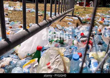 Belgrade, Serbia - June 25, 2017: Plastic bottles tossed by the metal fence. Used empty pet bottles thrown away and left on grass after an open air. - Stock Photo