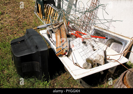Old TV set and the rest of bulky trash. Old TV thrown away next to a wall with a pile of mixed garbage. in natural environment. Recycling industry. - Stock Photo
